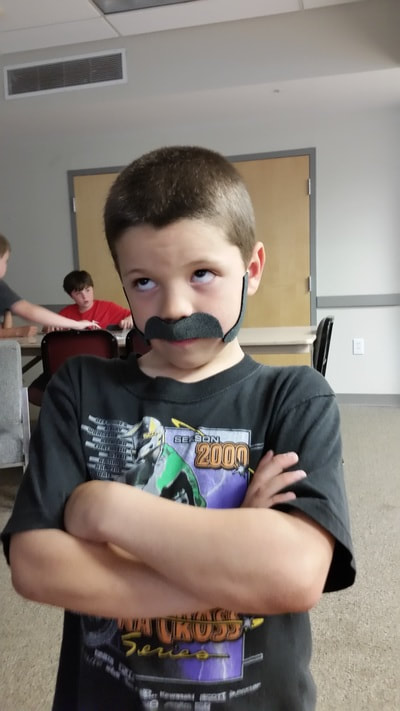 boy with fake beard making a face